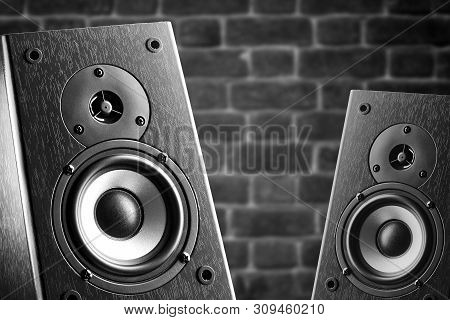 Dark Color Music Speakers. Loud Listening Music. Music Speakers On The Background Of A Brick Wall.