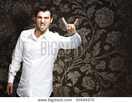portrait of a young man doing a rock symbol against a vintage wall