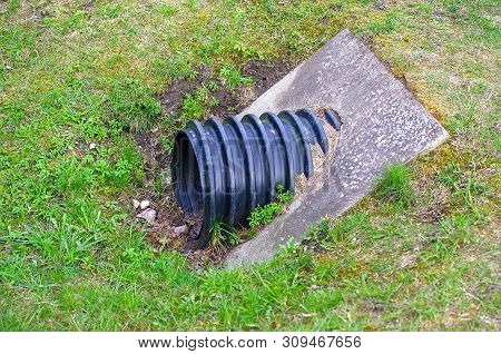 Plastic waste water drainage pipe. Sewage system. Industrial wastewater. Sewer drains from a plastic corrugated black sewer pipe into a sewer manhole in the city. Corrugate drainage pipe constuction