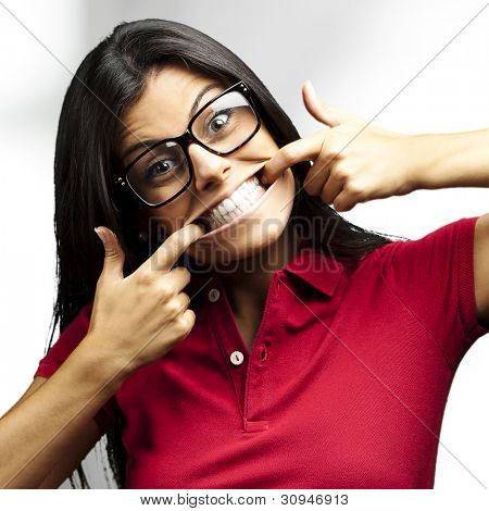 portrait of a happy young woman gesturing with her mouth indoor