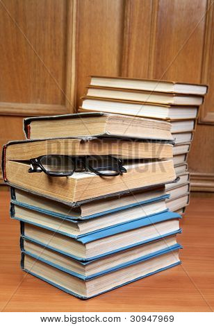 Two Piles Of Old Books And Glasses