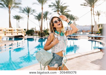 Graceful Girl In Sunglasses And Hat With Trendy Backpack Came To Pool For Sunbathing On Trestle-bed.