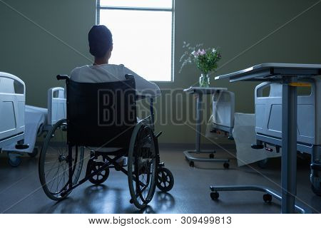 Rear view of disabled Mixed race female patient looking through window while sitting on wheelchair in hospital