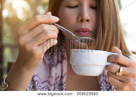 Young Woman Holding Drinking Coffee Using Spoon Blowing Hot Coffee Before Drinking In The Morning At