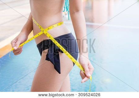 Woman In Sexy Bikini With Slim Body Measuring Thigh With Measurement Type After Diet With Swimming P