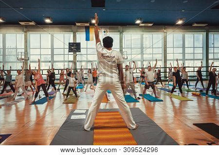 Kyiv, Ukraine: Yoga Teacher And Active People Performing Some Simple Asanas Together, Training In Sp
