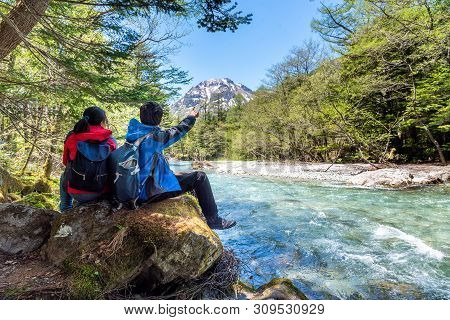 Man And Woman Sit On Rock Near Azusa River At Kamikochi In Northern Japan Alps.