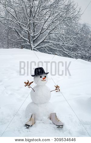 Snowman Gentleman In Winter Hat. Greeting Snowman. Cute Snowman At A Snowy Village. Snowman With Lig