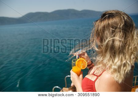 Happy Busty Woman On Yacht. Lady In Girl In Coral Bikini Holding Orange Fresh Drink. Cool Drink And