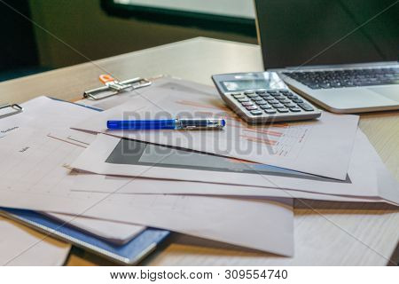 Unorganized Office Desk With Laptop Calculator And Paperwork