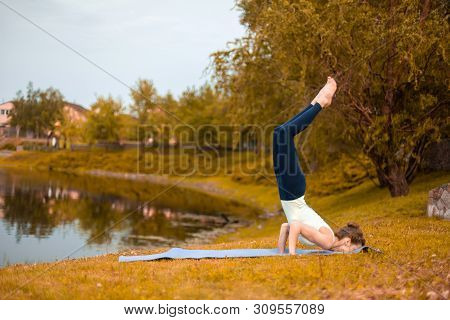 Slender Young Brunette Yogi Performs Challenging Yoga Exercises On The Green Grass In Autumn Against