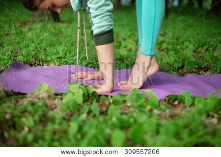 Thin Brunette Girl Plays Sports And Performs Yoga Poses In A Summer Park. Green Forest On The Backgr
