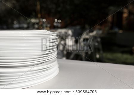 A Stack Of Clean White Plates Stands On A Table With A White Tablecloth In The Open Air. Buffet At T