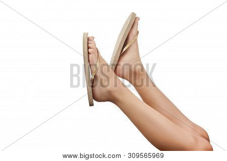 Young Girl Legs In Gold Flipflop Sandals Isolated On White