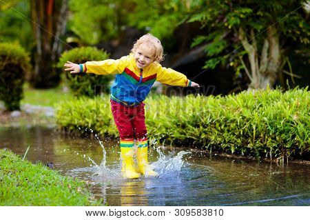 Child Playing In Puddle. Kids Jump In Autumn Rain