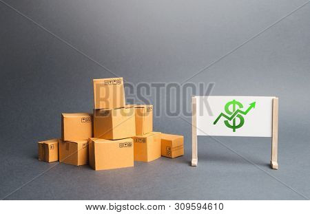 A Pile Of Cardboard Boxes And Whiteboard With Dollar Sign And Green Up Arrow. The Growth Rate Of Pro