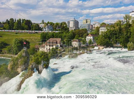 Laufen, Switzerland - June 7, 2019: The Rhine Falls Waterfall As Seen From The Laufen Castle, Buildi