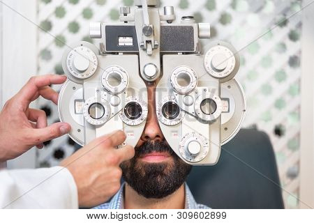Optometrist Doing Sight Testing For Male Patient In Clinic. Male Ophthalmologist Examining Patient M
