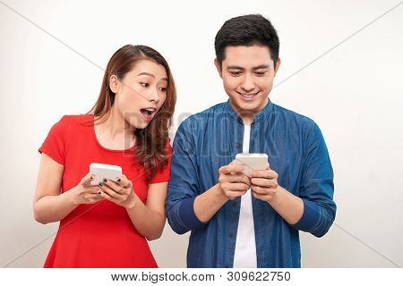 Asian Couple Using Gadgets: Pretty Girl Typing A Message On Cell Phone While Her Boyfriend Standing