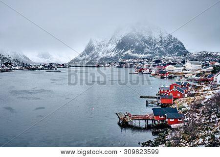 Reine fishing village on Lofoten islands with red rorbu houses in winter with snow. Lofoten islands, Norway