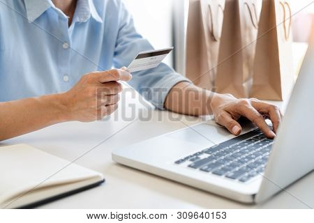 Man Holding Credit Card In Hand And Entering Security Code Using Smart Phone On Laptop Keyboard, Onl