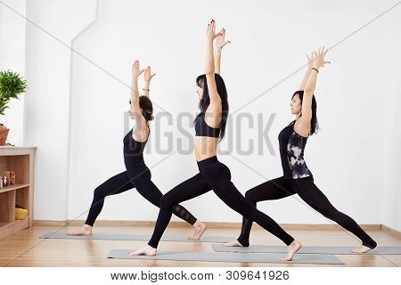 Side View Of Young Brunette Female Practicing Yoga Asana With Hands Up And Turning In One Direction.