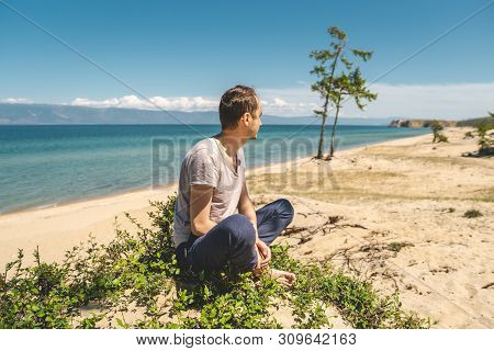 Man Traveler Relaxing On The Beach Of Olkhon Island Overlooking The Water Of The Lake And The Mounta