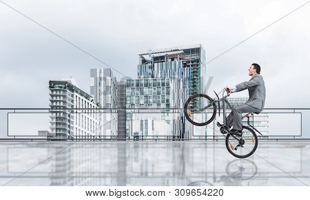 Man wearing business suit riding bicycle on penthouse balcony. Handsome cyclist popped wheelie on background of high office buildings. Terrace with modern downtown view. Outdoor fun and activity poster