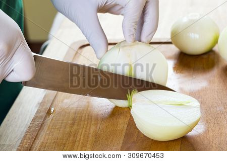 Man Cutting White Onion With Knife.