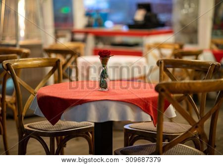 Close Up Of The Centerpiece Of A Spanish Restaurant Table With Red Checkered Tablecloth And Wood Cha