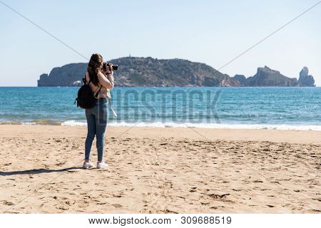 Back View Of Woman Taking Pictures With Dslr Camera Of Islands From The Beach - Medes Islands