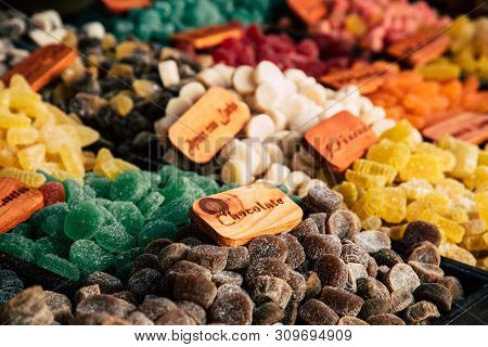 Colorful Sugar Sweets Gums And Jelly Beans On Market. Text On The Wooden Board: