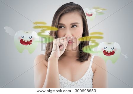 Asian Woman In White Dress Catch Her Nose Because Of A Bad Smell Against Gray Background - Halitosis