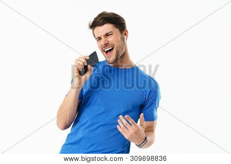 Photo closeup of joyful man in casual t-shirt singing and holding smartphone while wearing wireless earpods isolated over white background