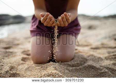 Kneel Girl Dropping Sand From Both Hands