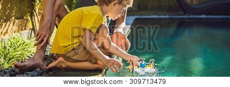 Dad And Son Playing With A Boat In The Pool Banner, Long Format