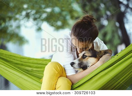 Young Woman In Green Hammock With Cute Dog Welsh Corgi In A Park Outdoors. Beautiful Happy Female In