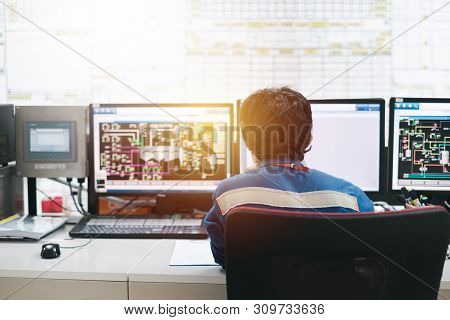 Professional Technician Sitting In Control Room Monitoring Process Petrochemical Plant, Asian Broad
