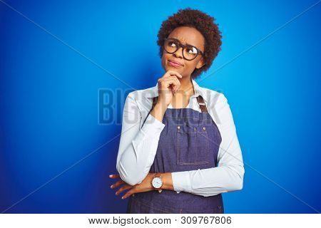 Young african american woman shop owner wearing business apron over blue background with hand on chin thinking about question, pensive expression. Smiling with thoughtful face. Doubt concept.