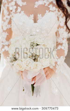 Beautiful Wedding Dress And Rose Flower Bouquet. Woman In White Clothing Suspension Holding Elegant