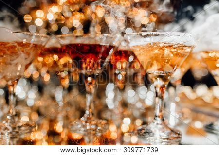Champagne Glasses With Smoking Special Effect. Bright Photo With Wedding Celebration Decoration Of B