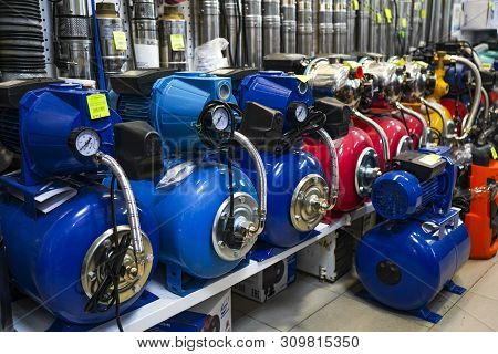 Chelyabinsk Region, Russia - June 2019. Plumbing Shop. Rack With Goods. Compressors And Water Pumps.