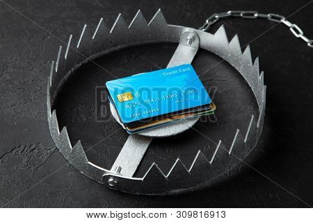 Trap With Stack Of Credit Cards. Unsafe Credit Risk. Black Background