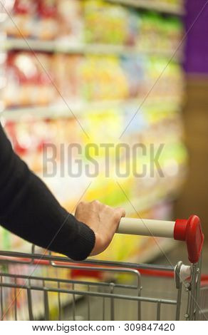 Woman Pushing A Shopping Cart In The Supermarket.