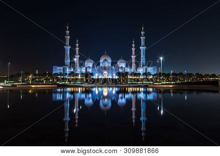 Iconic Islamic Site: Grand Mosque In Abu Dhabi, United Arab Emirates At Night With A Reflection In T