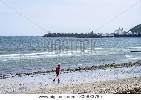 Douglas, Isle Of Man. Man Running At The Beach With Cruise Ship Close To Shore. Powerful Runner Trai
