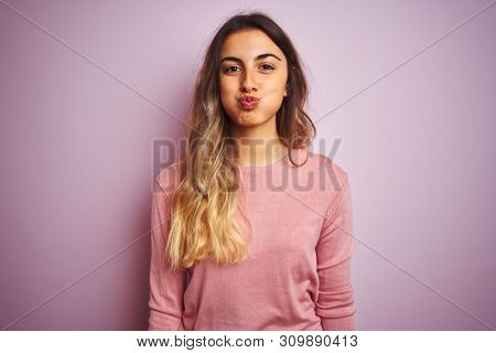 Young beautiful woman wearing a sweater over pink isolated background puffing cheeks with funny face. Mouth inflated with air, crazy expression.