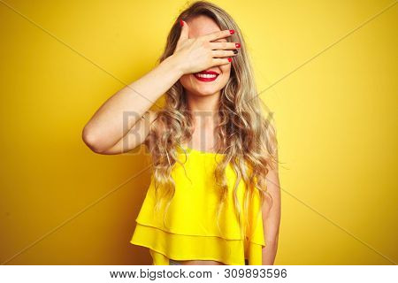 Young attactive woman wearing t-shirt standing over yellow isolated background smiling and laughing with hand on face covering eyes for surprise. Blind concept.