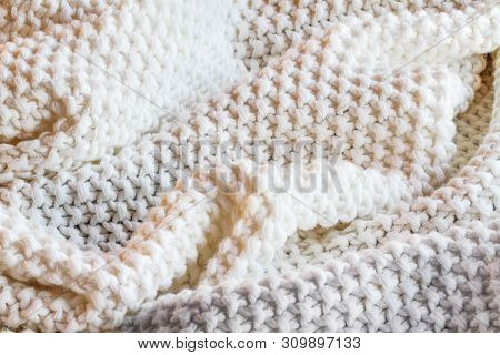 Abstract Of A Soft Knit White And Grey Throw Blanket With Selective Focus In Center With Blurred Edg