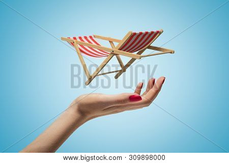 Side Closeup Of Womans Hand Facing Up And Levitating Small Striped Chaise-longue On Light Blue Gradi